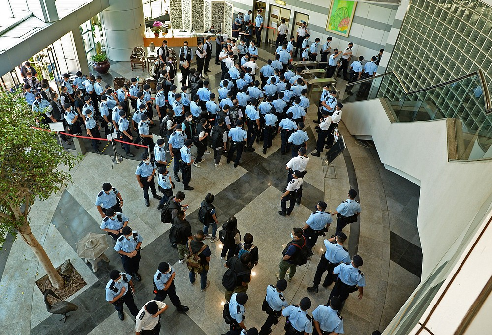 Police officers gather at the lobby of headquarters of Apple Daily in Hong Kong Thursday, June 17, 2021. Hong Kong police on Thursday morning arrested the chief editor and four other senior executives of Apple Daily under the national security law on suspicion of collusion with a foreign country to endanger national security, according to local media reports. (Apple Daily via AP)