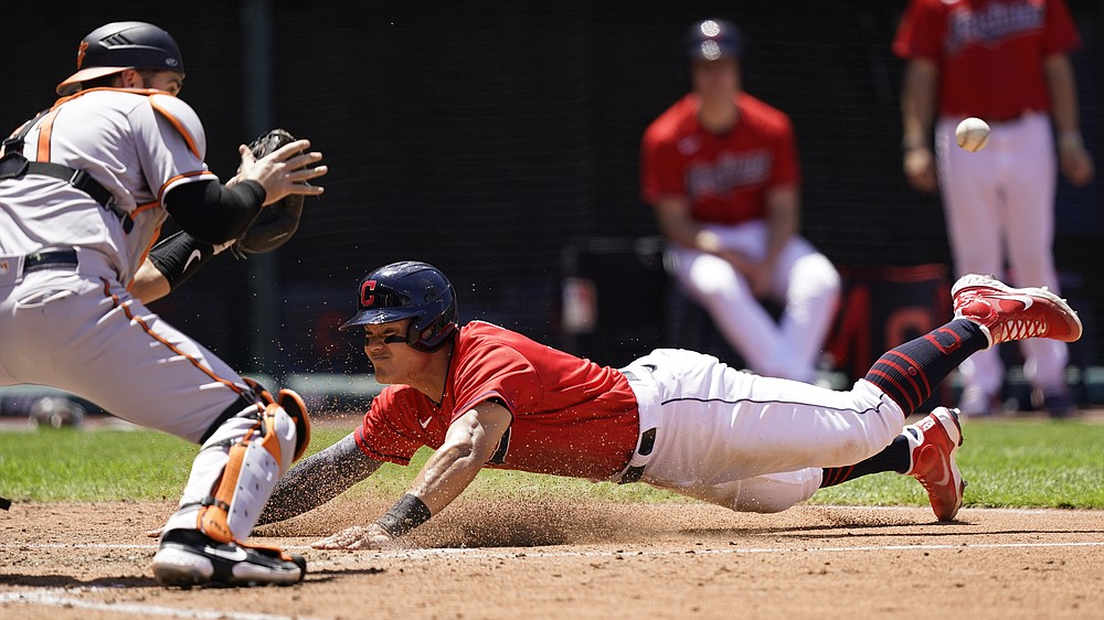 Cleveland Indians' Yu Chang, right, slides safely into home plate as Baltimore Orioles' Austin Wynns waits of the ball in the fourth inning of a baseball game, Thursday, June 17, 2021, in Cleveland. (AP Photo/Tony Dejak)