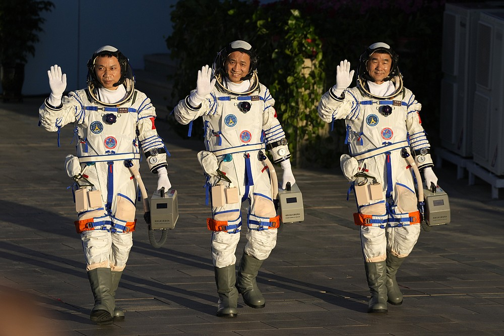 Chinese astronauts, from left, Tang Hongbo, Nie Haisheng, and Liu Boming wave as they prepare to board for liftoff at the Jiuquan Satellite Launch Center in Jiuquan in northwestern China, Thursday, June 17, 2021. China plans on Thursday to launch three astronauts onboard the Shenzhou-12 spaceship who will be the first crew members to live on China's new orbiting space station Tianhe, or Heavenly Harmony. (AP Photo/Ng Han Guan)