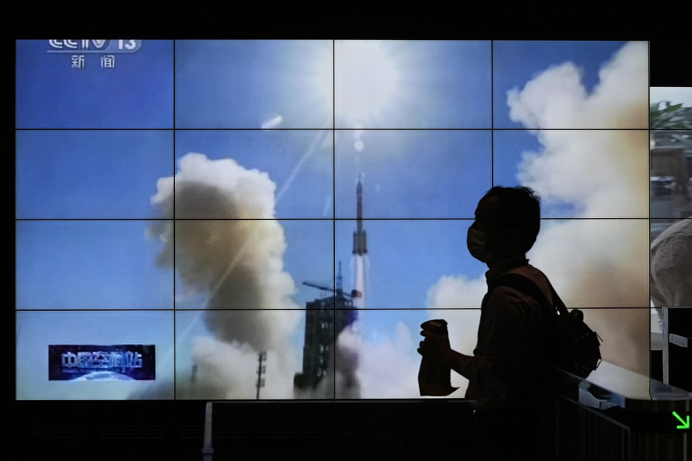 A man is silhouetted as she walks by a TV screen showing CCTV live telecast of the Long March-2F Y12 rocket carrying a crew of Chinese astronauts in a Shenzhou-12 spaceship lifts off at the Jiuquan Satellite Launch Center, at a shopping mall in Beijing, Thursday, June 17, 2021. China launched the first three crew members on a mission to its new space station Thursday in its first crewed mission in five years. (AP Photo/Andy Wong)