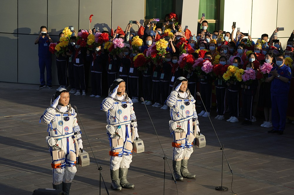Chinese astronauts, from left, Tang Hongbo, Nie Haisheng, and Liu Boming salute as they prepare to board for liftoff at the Jiuquan Satellite Launch Center in Jiuquan in northwestern China, Thursday, June 17, 2021. China plans on Thursday to launch three astronauts onboard the Shenzhou-12 spaceship who will be the first crew members to live on China's new orbiting space station Tianhe, or Heavenly Harmony. (AP Photo/Ng Han Guan)