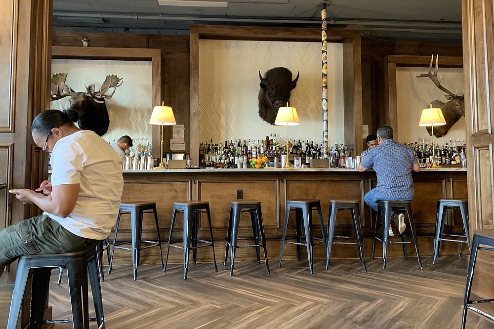 Stuffed moose, bison and deer heads decorate the wall behind the bar at Cannibal & Craft. (Arkansas Democrat-Gazette/Eric E. Harrison)