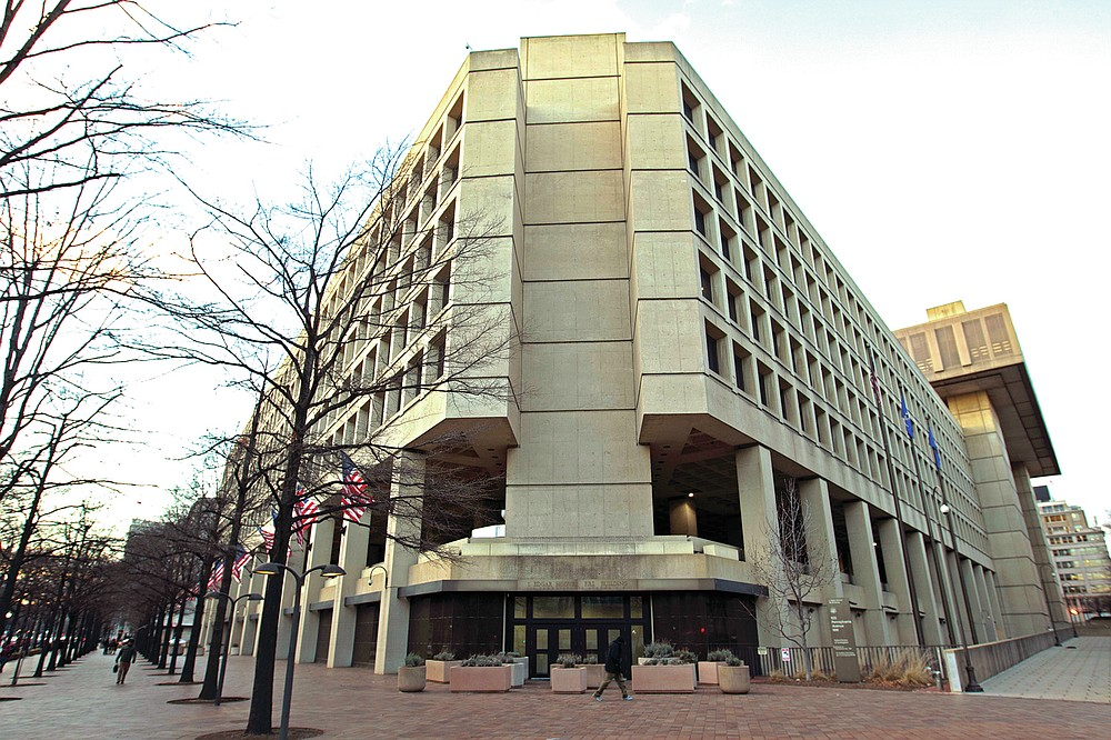 This Friday, Feb. 2, 2018 file photo shows the Federal Bureau of Investigation building in Washington. On Friday, June 18, 2021, The Associated Press reported on a video circulating online incorrectly asserting the FBI headquarters building in Washington is completely closed, empty and walled off. A video spreading the false claim shows the back of the building rather than the main entrance, which was open and fully operational this week, according to a statement from the FBI and the observations of an AP reporter based nearby. (AP Photo/Jose Luis Magana, File)