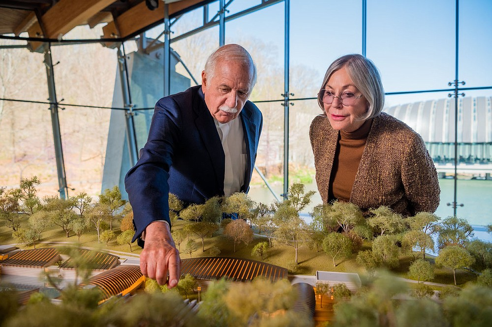 Moshe Safdie, Founder Safdie Architects and Alice Walton Crystal Bridges Founder and Board chairperson look over the diorama of a planned 100,000 square foot expansion of the museum in the Great Hall at Crystal Bridges Museum of American Art in Bentonville, Arkansas. (Special to the Arkansas Democrat-Gazette)