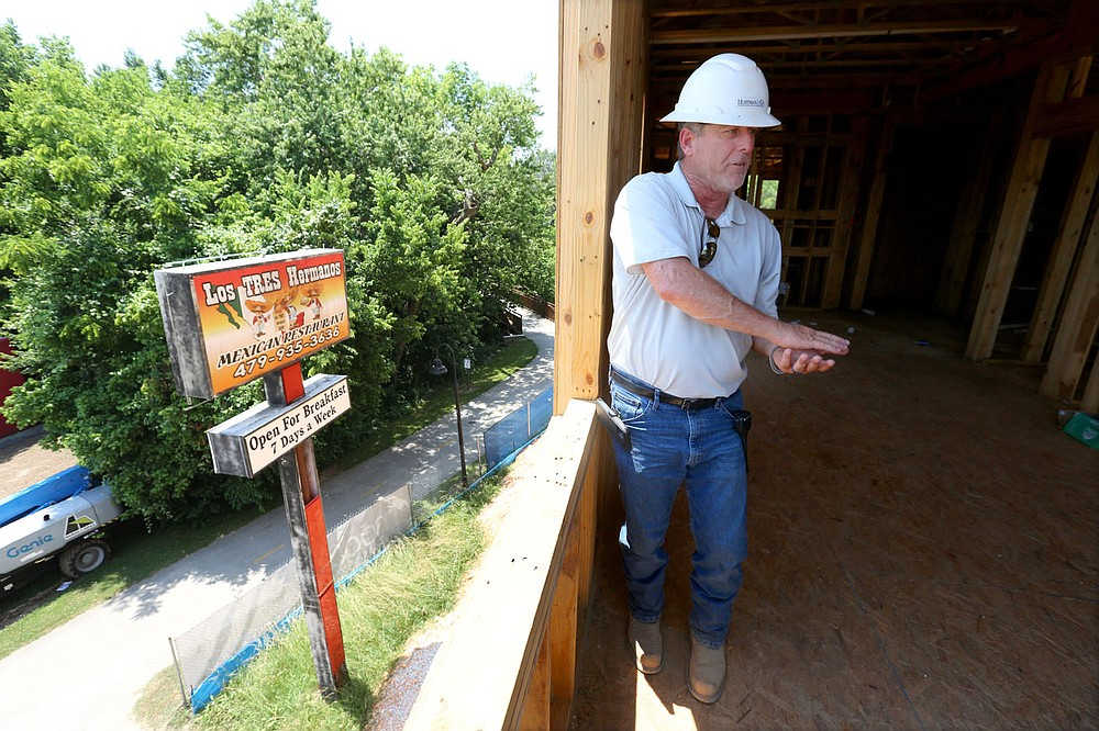 Shaun Brock, project superintendent with Huffman and Company, discusses Thursday, June 17, 2021, the decision to keep the Los Tres Hermanos Mexican Restaurant sign that was formerly located on the site of the South Yard as he walks through a phase of the apartment construction on the site in Fayetteville. The project lies between elements of the city's U.S. 71B corridor project to the east and the University of Arkansas Windgate Art and Design District to the west, and plans to open apartments for lease early next year. Check out nwaonline.com/210620Daily/ and nwadg.com/photos for a photo gallery. (NWA Democrat-Gazette/David Gottschalk)