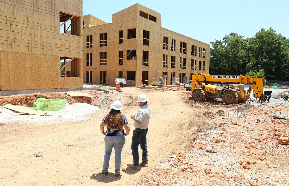 Sarah King (left), communications manager at Specialized Real Estate Group, and Shaun Brock, project superintendent with Huffman and Company, discuss the amenities Thursday, June 17, 2021, that will be available at the South Yard as they walk through a phase of the apartment construction on the site in Fayetteville. The project lies between elements of the city's U.S. 71B corridor project to the east and the University of Arkansas Windgate Art and Design District to the west, and plans to open apartments for lease early next year. Check out nwaonline.com/210620Daily/ and nwadg.com/photos for a photo gallery. (NWA Democrat-Gazette/David Gottschalk)