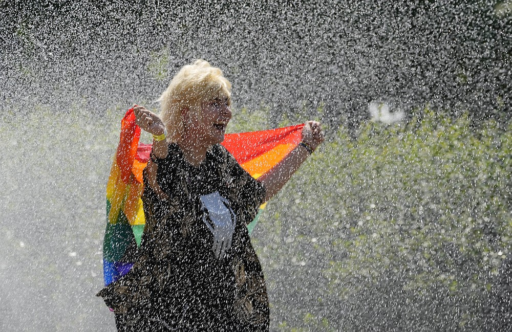 A woman with a rainbow flag cools off in a sprinkler ahead of the Equality Parade, the largest LGBT pride parade in Central and Eastern Europe, in Warsaw, Poland, Saturday, June 19, 2021.(AP Photo/Czarek Sokolowski)