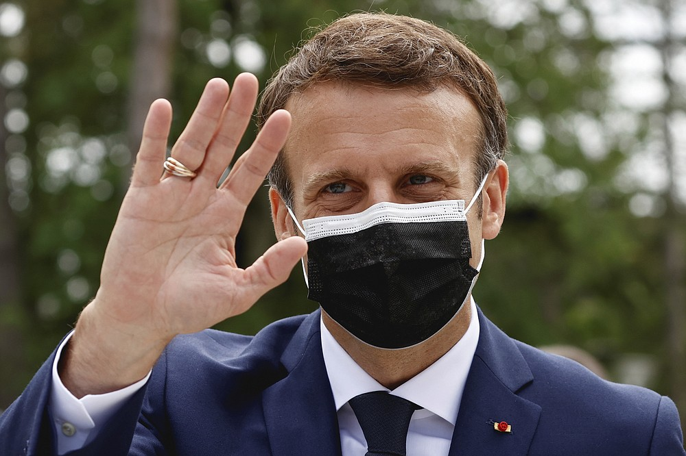 French President Emmanuel Macron waves during the first round of French regional and departmental elections, in Le Touquet-Paris-Plage, northern France, Sunday, June 20, 2021. The elections for leadership councils of France's 13 regions, from Brittany to Burgundy to the French Riviera, are primarily about local issues like transportation, schools and infrastructure. But leading politicians are using them as a platform to test ideas and win followers ahead of the April presidential election. (Christian Hartmann/Pool via AP)