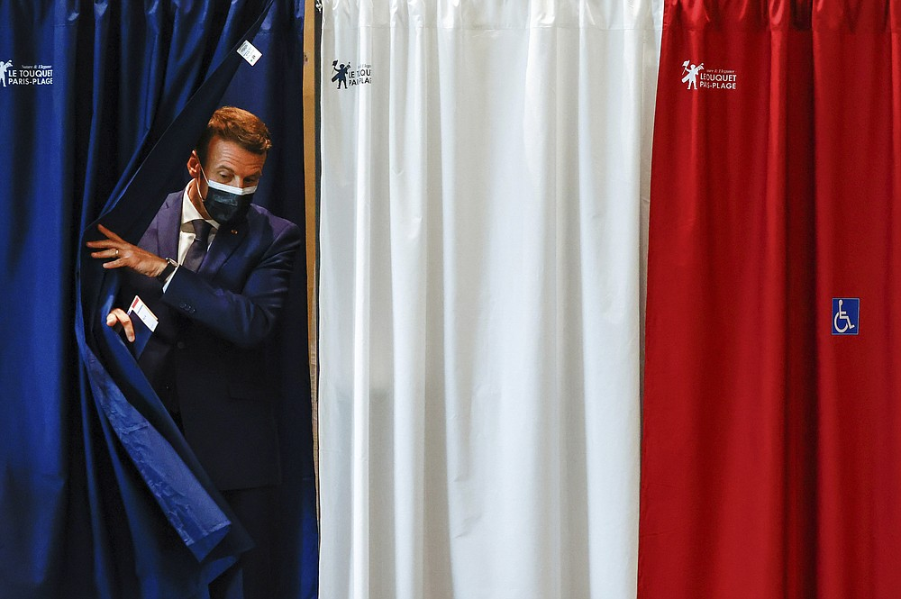 French President Emmanuel Macron leaves the voting booth during the first round of French regional and departmental elections, in Le Touquet-Paris-Plage, northern France, Sunday, June 20, 2021. The elections for leadership councils of France's 13 regions, from Brittany to Burgundy to the French Riviera, are primarily about local issues like transportation, schools and infrastructure. But leading politicians are using them as a platform to test ideas and win followers ahead of the April presidential election. (Christian Hartmann/Pool via AP)
