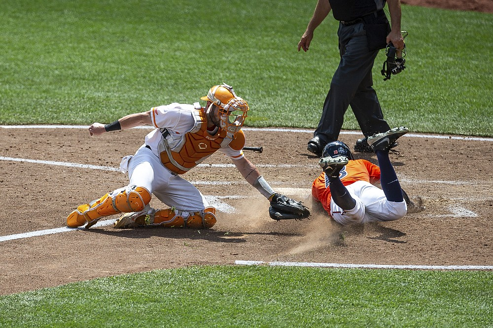 Virginia infielder Alex Tappen, front right, slides to home for a run against Tennessee catcher Connor Pavolony, left, in the seventh inning during a baseball game in the College World Series, Sunday, June 20, 2021, at TD Ameritrade Park in Omaha, Neb. (AP Photo/John Peterson)