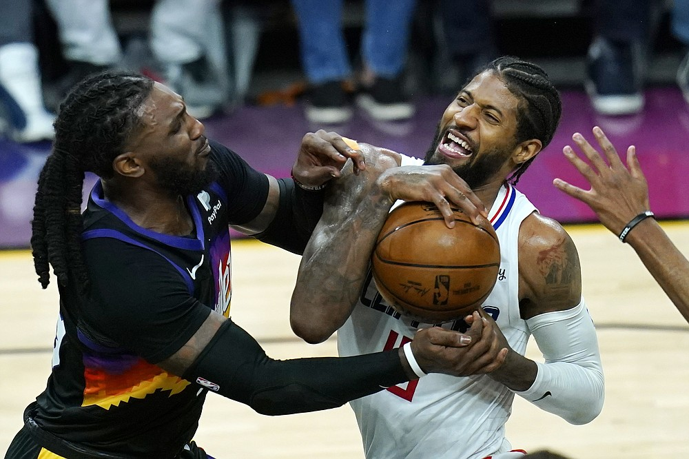 Los Angeles Clippers guard Paul George, right, reacts as he is stopped in the lane by Phoenix Suns forward Jae Crowder, left, during the second half of Game 1 of the NBA basketball Western Conference finals Sunday, June 20, 2021, in Phoenix. (AP Photo/Ross D. Franklin)
