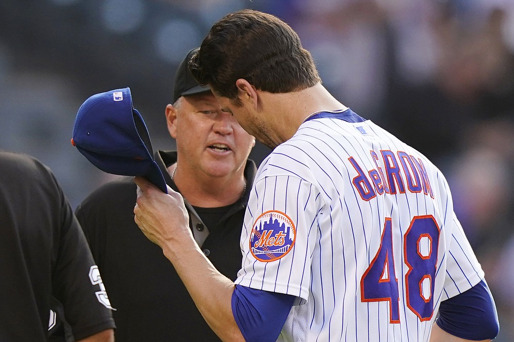 Third baseman Ron Kulpa, left, looks inside the cap of New York Mets starting pitcher Jacob deGrom (48) after deGrom pitched in the start of the fifth inning of a baseball game against the Atlanta Braves on Monday, June 21, 2021, in New York City.  (AP Photo / Kathy Willens)