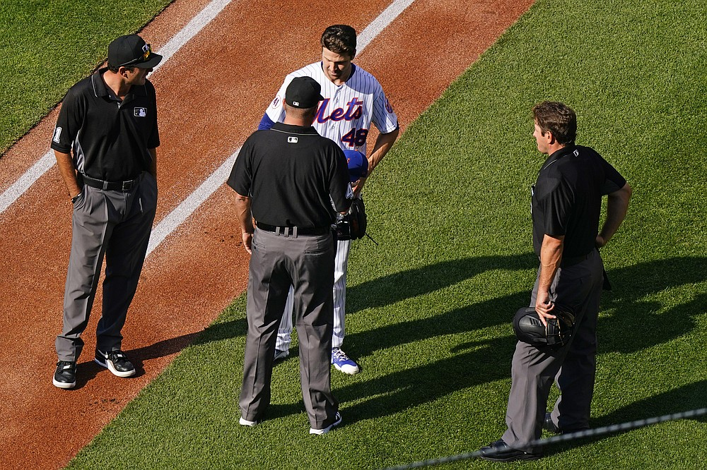 Third baseman Ron Kulpa, bottom center, quizzes New York Mets starter Jacob deGrom, top center, about foreign substances before deGrom heads for the dugout after pitching the first inning in a baseball game against the Atlanta Braves on Monday, June 21, 2021, in New York City.  Home plate umpire Ben May, right, watches.  (AP Photo / Kathy Willens)