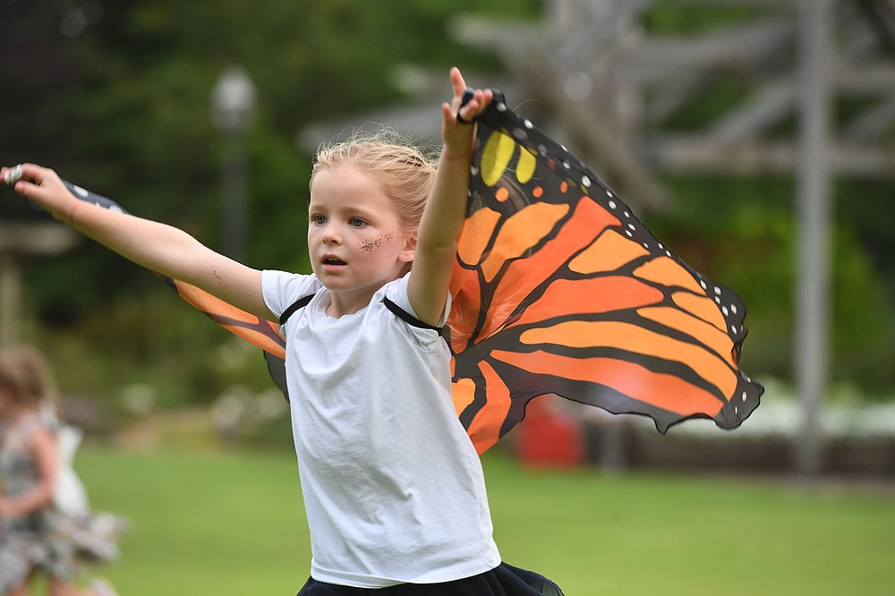 Evie East, 5, catches air under her wings Tuesday July 14, 2020 at the Botanical Garden of the Ozarks in Fayetteville. In place of the Firefly Fling Festival, which was canceled due to covid-19, the garden is hosting Magical Evenings in the Garden during the week of July 12 - 18. The garden will be open from 6:30 to 8:30 pm. Guests are invited to wear their fairy wings or costumes, bring picnics, and enjoy the garden in the cool of the evening. In order to allow proper social distancing, guest capacity will be limited. Face coverings will be required and guests must maintain a minimum of six feet from others.. To reserve space visit the garden's website at www.bgozarks.org. Evie was at the garden with her parents Cash and Bright East of Fayetteville. Visit nwaonline.com/200715Daily/ for photo galleries. (NWA Democrat-Gazette/J.T. Wampler)