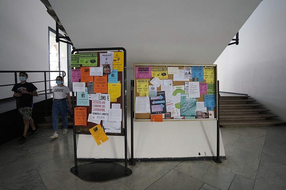 Students walk past a billboard with notices in a hallway of Milan's Statale University, northern Italy, Monday, June 21, 2021. Backed by 261 billion euros from the EU and Italian government, the country's recovery plan calls for a top-to-bottom shakeup of a major industrial economy long hampered by red tape, a fear of change, and bureaucratic and educational inertia.  Leading the charge is Premier Mario Draghi, the former head of the European Central Bank, who was tapped as head of a national unity government specifically for his economic expertise and institutional knowledge both in Italy and the EU.A key target is keeping more young Italians from taking their know-how abroad, a perennial issue in Italy, which has one of the lowest rates of university graduates in Europe and one of the largest brain drains.  (AP Photo/Antonio Calanni)