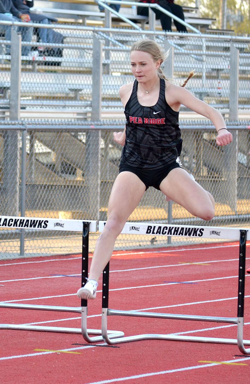 Blakelee Winn clears a hurdle Friday, April 9, in the Blackhawk Relays in Pea Ridge.