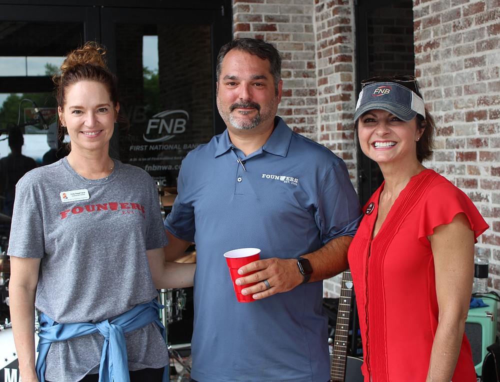 Emily Rappe Fisher, CSC development director (from left), visits with Courtney Silkwood and Tanya Mims of First National Bank of Northwest Arkansas at the Crawfish Boil on June 5. (NWA Democrat-Gazette/Carin Schoppmeyer)