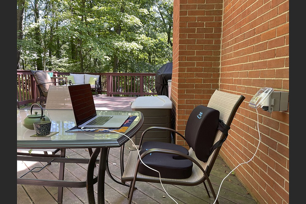 A lumbar pillow and seat cushion added to an outdoor dining chair create a more ergonomic outdoor workspace. (Melissa Rayworth via AP)