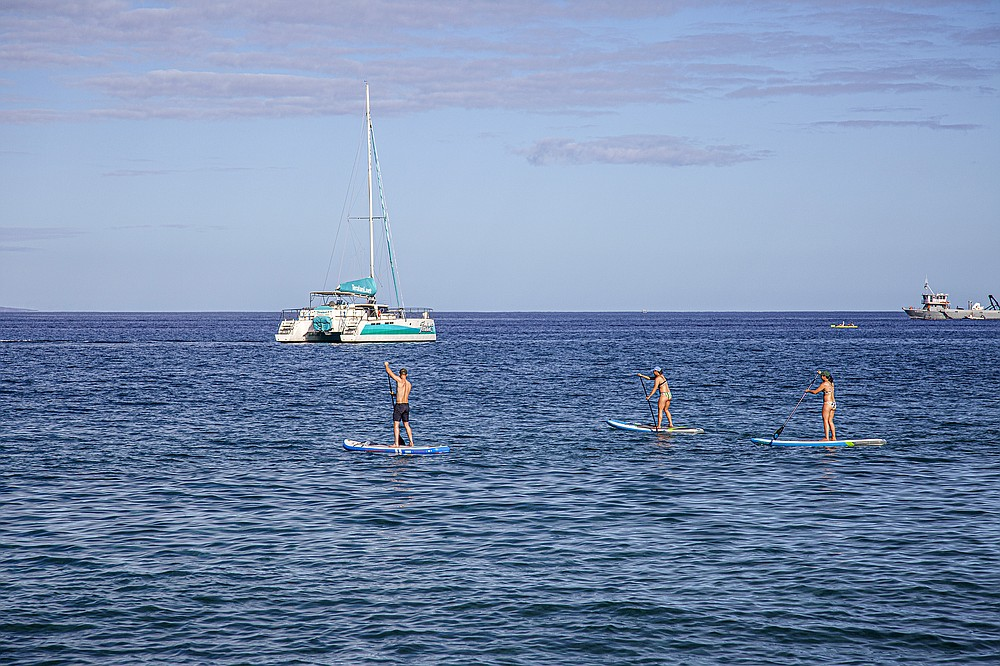 Paddleboarders stay close to the shore on Maui. (Photo for The Washington Post/Ryan Siphers)