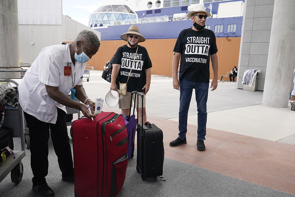 Porter Johnny Jones Jr. tags the luggage of Celebrity Cruise passengers James and Cynthia Mitchell of Kansas, Saturday, June 26, 2021, in Fort Lauderdale, Fla. Celebrity Edge is the first cruise ship to leave a U.S. port since the coronavirus pandemic brought the industry to a 15-month standstill. The cruise ship has 40 percent capacity, and with virtually all passengers vaccinated against COVID-19. (AP Photo/Marta Lavandier)