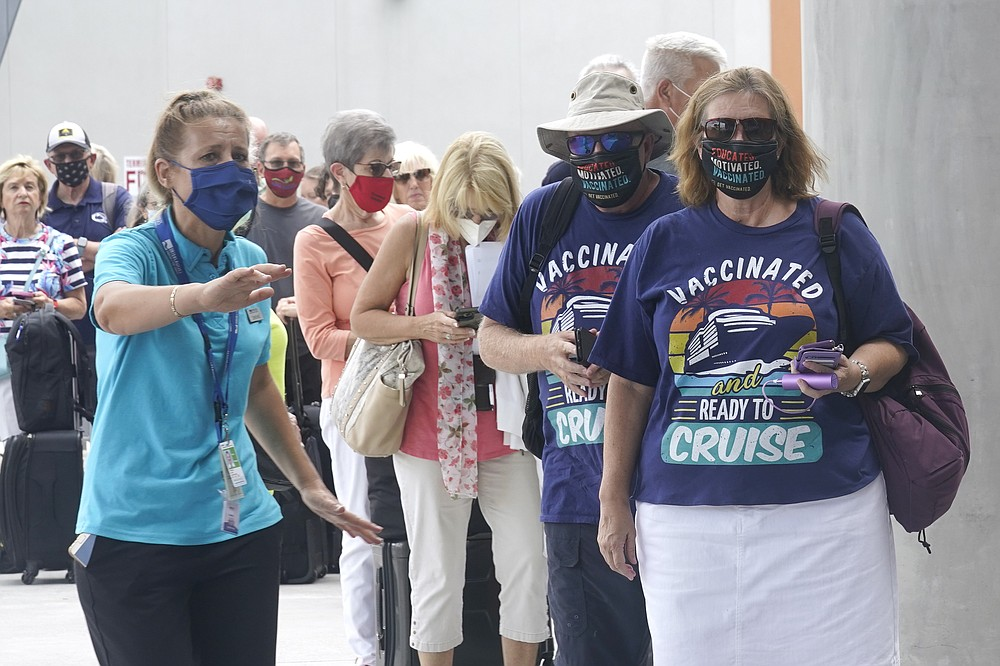 Orchid Klaric, left, assists Brenda and Kurt Duncan of Denver, with checking into their cruise, Saturday, June 26, 2021, in Fort Lauderdale, Fla. Celebrity Edge is the first cruise ship to leave a U.S. port since the coronavirus pandemic brought the industry to a 15-month standstill. The seven-night cruise will have 40 percent capacity and with virtually all passengers vaccinated against COVID-19. (AP Photo/Marta Lavandier)