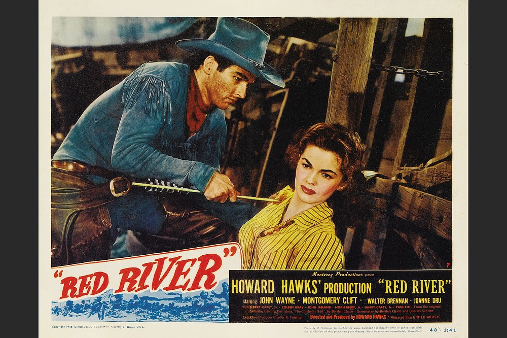 """Matt Garth (Montgomery Clift) extracts an arrow that has pierced the shoulder of Tess Millay (Joanne Dru) in this image from the movie """"Red River."""""""