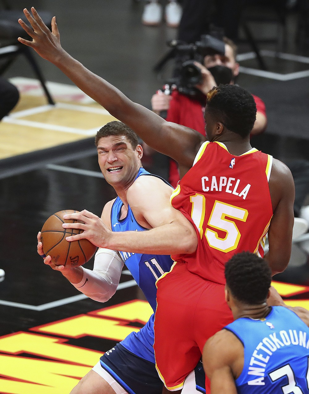 Atlanta Hawks center Clint Capela fouls Milwaukee Bucks center Brook Lopez, left, during the second quarter in Game 3 of the NBA Eastern Conference basketball finals, Sunday, June 27, 2021, in Atlanta. (Curtis Compton/Atlanta Journal-Constitution via AP)