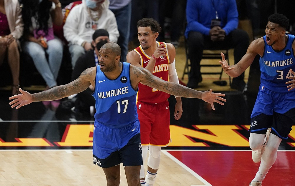 Milwaukee Bucks' P.J. Tucker (17) and Giannis Antetokounmpo (34) react to a play during the first half of Game 3 of the NBA Eastern Conference basketball finals Sunday, June 27, 2021, in Atlanta. (AP Photo/Brynn Anderson)