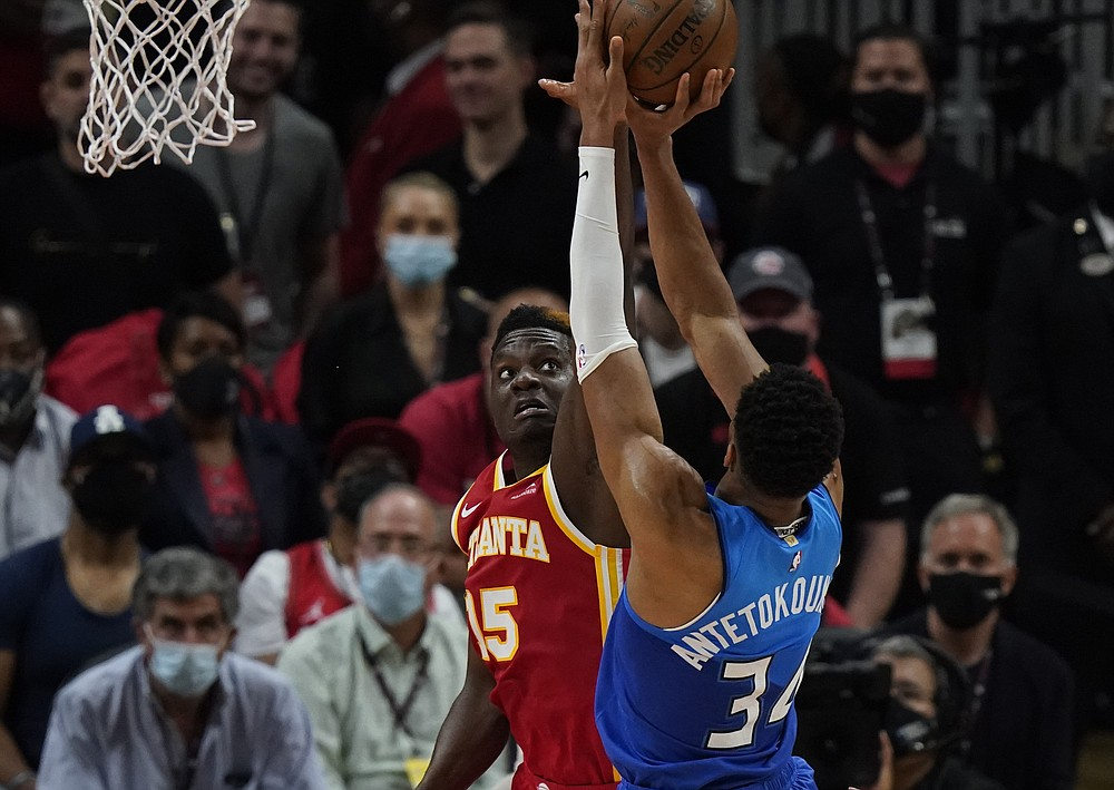 Atlanta Hawks' Clint Capela (15) attempts to block the ball against Milwaukee Bucks' Giannis Antetokounmpo (34) during the first half of Game 3 of the NBA Eastern Conference basketball finals Sunday, June 27, 2021, in Atlanta. (AP Photo/Brynn Anderson)