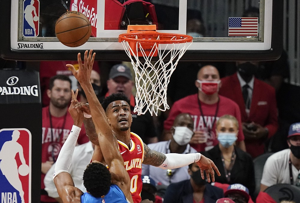 Atlanta Hawks' John Collins (20) blocks a shot by Milwaukee Bucks' Giannis Antetokounmpo during the first half of Game 3 of the NBA Eastern Conference basketball finals Sunday, June 27, 2021, in Atlanta. (AP Photo/Brynn Anderson)