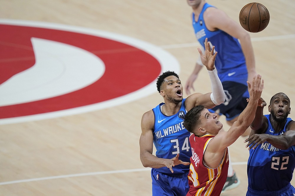 Atlanta Hawks' Bogdan Bogdanovic (13) rebounds the ball against Milwaukee Bucks' Khris Middleton (22) and Giannis Antetokounmpo (34) during the first half of Game 3 of the NBA Eastern Conference basketball finals Sunday, June 27, 2021, in Atlanta. (AP Photo/Brynn Anderson)