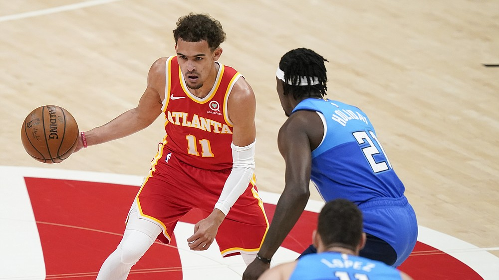 Atlanta Hawks' Trae Young (11) dribbles against Milwaukee Bucks' Jrue Holiday (21) during the first half of Game 3 of the NBA Eastern Conference basketball finals Sunday, June 27, 2021, in Atlanta. (AP Photo/Brynn Anderson)
