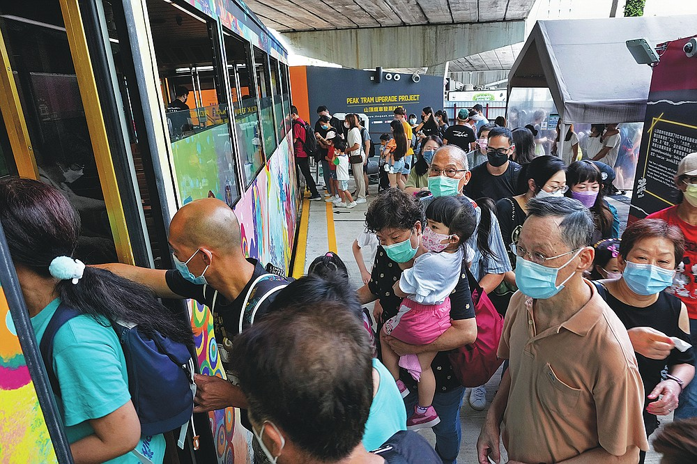 Passengers get on a Peak Tram in Hong Kong on June 17, 2021. Hong Kong's Peak Tram is a fixture in the memories of many residents and tourists, ferrying passengers up Victoria Peak for a bird's eye view of the city's many skyscrapers. (AP Photo/Vincent Yu)