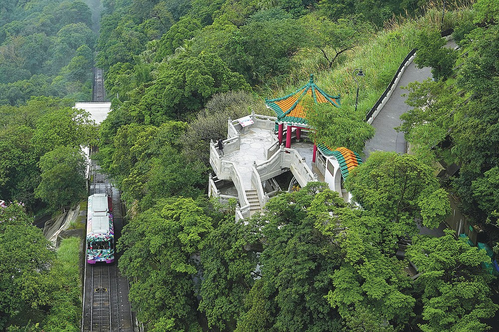 A Peak Tram passes uphill of the Victoria Peak in Hong Kong on June 17, 2021. Hong Kong's Peak Tram is a fixture in the memories of many residents and tourists, ferrying passengers up Victoria Peak for a bird's eye view of the city's many skyscrapers. (AP Photo/Vincent Yu)