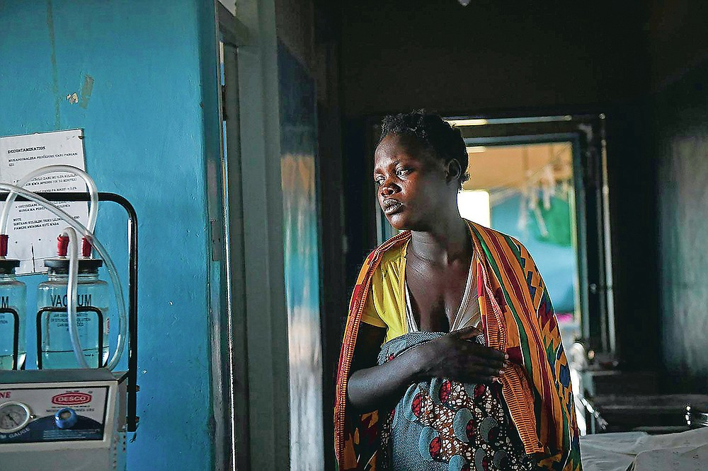 A woman in labour, walks to her delivery bed at Malawi Government's Mauwa Health Centre labour ward in Chiradzulu, southern Malawi, Sunday, May 23, 2021 . Health officials in Malawi say fewer women are getting prenatal care amid the COVID-19 pandemic. At risk are the developing country's gains on its poor rate of maternal deaths. (AP Photo/Thoko Chikondi)