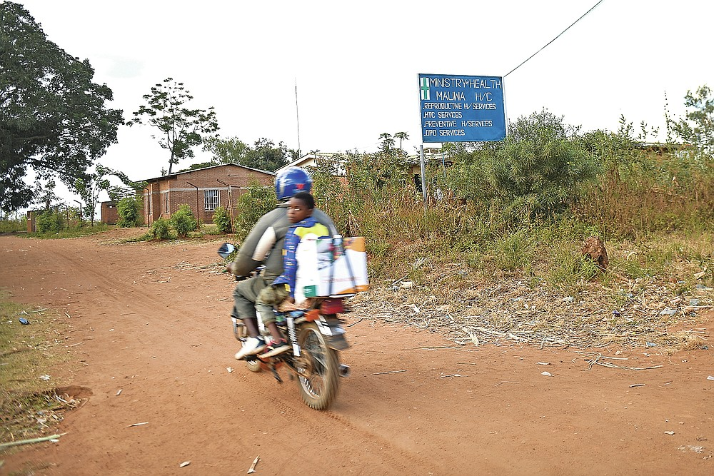 People on a motorbike ride near Malawi Government's Mauwa Health Centre, in Chiradzulu, southern Malawi on Wednesday, May 26, 2021, Health officials in Malawi say fewer women are getting prenatal care amid the COVID-19 pandemic. At risk are the developing country's gains on its poor rate of maternal deaths. (AP Photo/Thoko Chikondi)