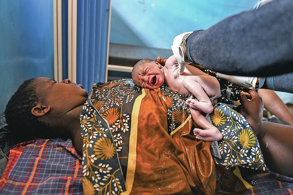 A baby boy cries soon after birth, at the Malawi Government's Mauwa Health Centre in Chiradzulu southern Malawi on Wednesday May 26, 2021. Health officials in Malawi say fewer women are getting prenatal care amid the COVID-19 pandemic. At risk are the developing country's gains on its poor rate of maternal deaths. (AP Photo/Thoko Chikondi)