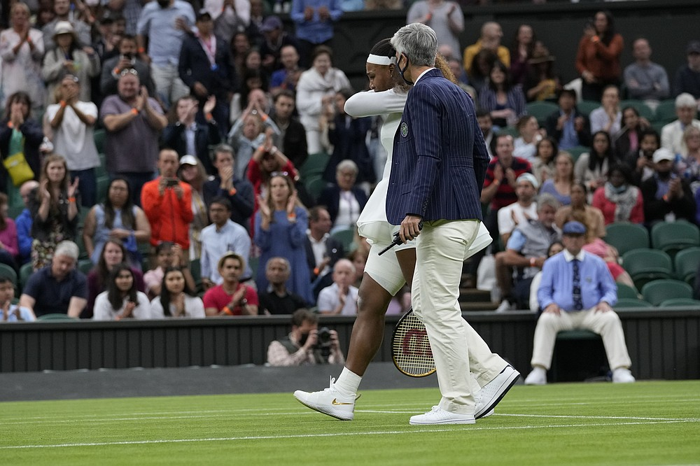 Un arbitru o ajută pe Serena Williams din America să iasă de pe teren după ce s-a retras din meciul din prima rundă feminin la feminin împotriva Belarusiei Alexandra Sasnovich în ziua a doua a turneului de tenis de la Wimbledon din Londra, marți, 29 iunie 2021 (Foto AP / Kirsty Wigglesworth)
