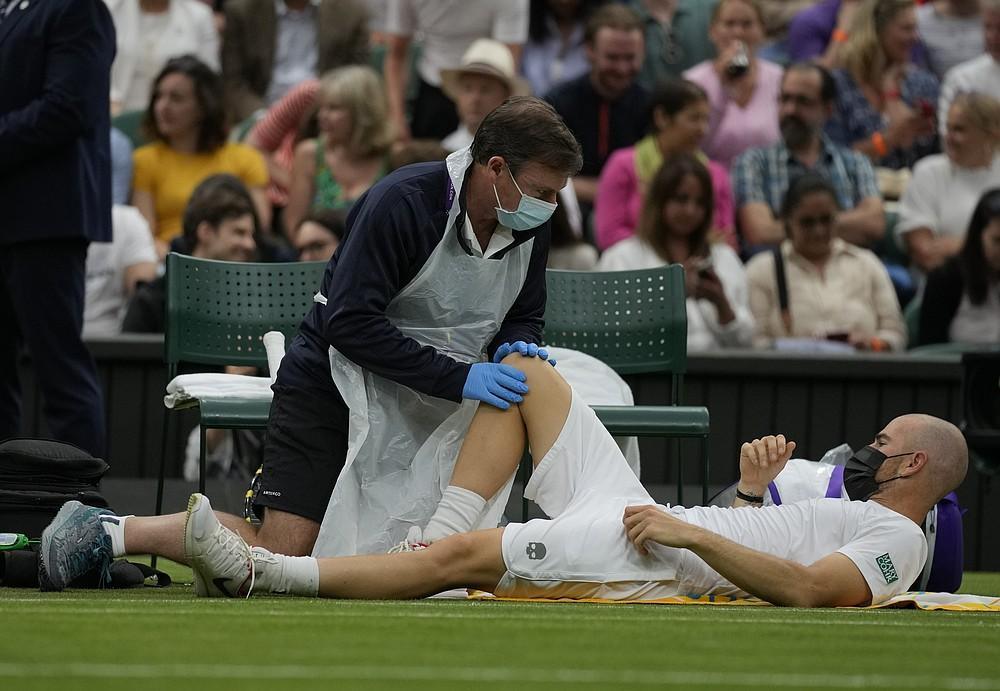 Adrien Mannarino, din Franța, primește îngrijiri medicale în timpul meciului din prima rundă individuală masculină împotriva lui Roger Federer în ziua a doua a Campionatelor de tenis de la Wimbledon de la Londra, marți, 29 iunie 2021 (Foto AP / Kirsty Wigglesworth)