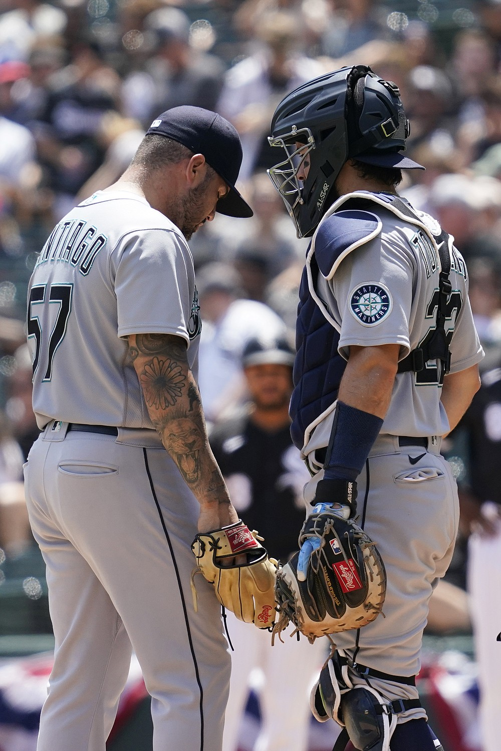 Seattle Mariners catcher Luis Torrens, right, talks with relief pitcher Hector Santiago during the fifth inning in the first baseball game of a doubleheader against the Chicago White Sox in Chicago, Sunday, June 27, 2021. (AP Photo/Nam Y. Huh)