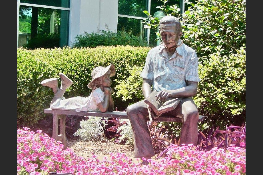 A sculpture by Randolph Rose of a man reading to a child graces Hays Senior Center. (Special to the Democrat-Gazette/Marcia Schnedler)