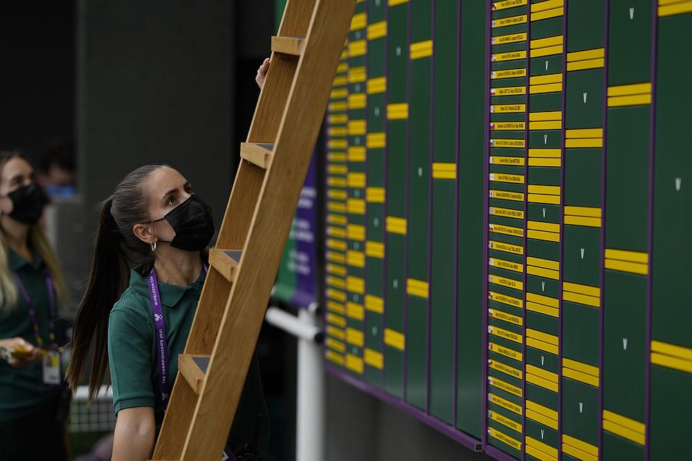 Сотрудник размещает информацию на табло на теннисных кортах Уимблдона в Лондоне, в четверг, 1 июля 2021 г. (AP Photo / Alastair Grant)