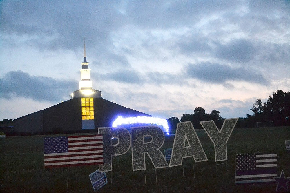 Blue lights twinkle on the church sign behind flags and a sign memorializing slain Pea Ridge Police Officer Kevin Apple at First Baptist Church, Slack Street, Pea Ridge, just before dawn Friday, as a message to the law enforcement members traveling through town in the funeral processional Friday morning.