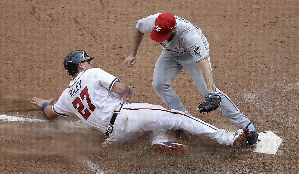 The Atlanta Braves' Austin Riley (27) slips into home plate as Anthony Bass of the Miami Marlins hits a tag in the 10th inning of a baseball game on Sunday, July 4, 2021 in Atlanta.  After a review of the game, the field decision was overturned and Riley was called.  (AP Photo / Ben Margot)