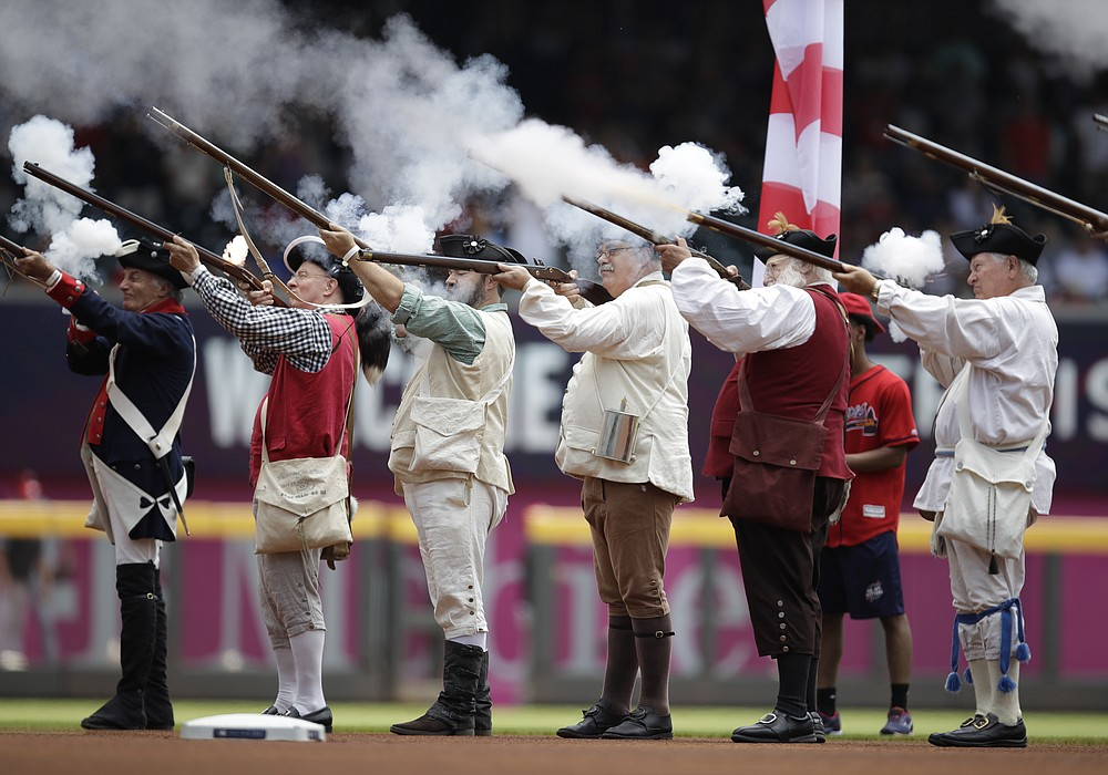 Men dressed as Revolutionary War soldiers fire a volley before the National Anthem ahead of the Atlanta Braves-Miami Marlins baseball game on Sunday, July 4, 2021, in Atlanta.  (AP Photo / Ben Margot)