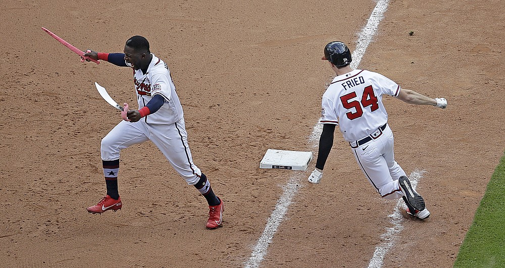 Atlanta Braves' Max Fried (54) rounds off the opening goal after hitting the winning shot against the Miami Marlins as Guillermo Heredia, left, storms the pitch in the 10th inning of a baseball game on Sunday, July 4, 2021, in Atlanta.  (AP Photo / Ben Margot)
