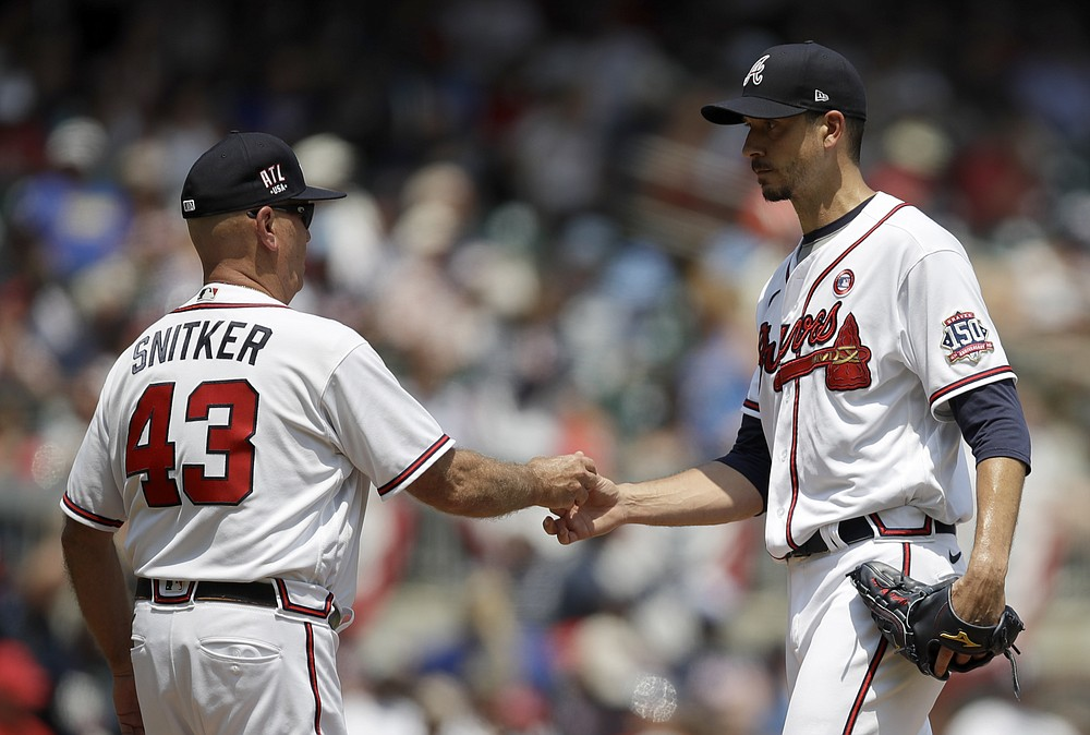 Atlanta Braves pitcher Charlie Morton, right, hands the ball to manager Brian Snitker (43) during the sixth inning of a baseball game against the Miami Marlins on Sunday, July 4, 2021, in Atlanta.  (AP Photo / Ben Margot)