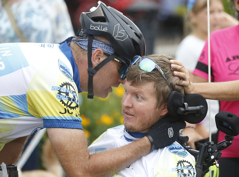 Josh Fohner is surrounded by teammates, well wishers and friends Thursday, July 1, 2021, after arriving at Shiloh Square in downtown Springdale. Fohner, the inspiration behind the All In For Josh Ride, was finishing up a 908 mile bicycle ride that started in Buena Vista, CO. to Springdale. The Springdale native was seriously injured in a biking accident in 2016 and suffered severe brain injuries. Check out nwaonline.com/210702Daily/ and nwadg.com/photos for a photo gallery.(NWA Democrat-Gazette/David Gottschalk)