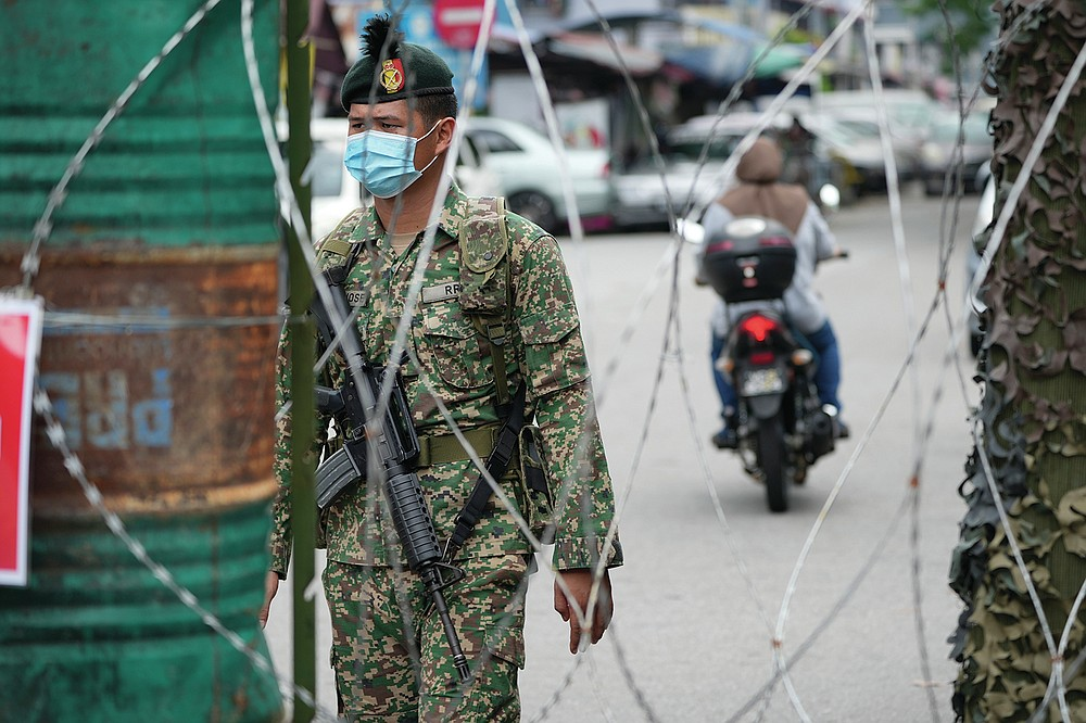 A soldier stands guard near barbwire at Kerinchi area placed under the enhanced movement control order (EMCO) due to drastic increase in the number of COVID-19 cases recorded in Kuala Lumpur, Malaysia, Sunday, July 4, 2021. Malaysia starts further tightening movement curbs and imposes a curfew in most areas in its richest state Selangor and parts of Kuala Lumpur, where coronavirus cases remain high despite a national lockdown last month. (AP Photo/Vincent Thian)