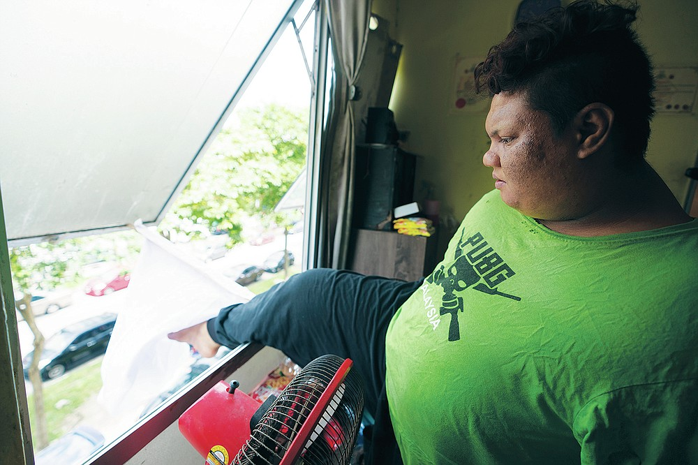 Mohamad Nor Abdullah, born without arms, adjusts a white flag outside the window of his rented room in Kuala Lumpur, Malaysia on July 3, 2021. When Mohamad Nor put a white flag outside his window late at night, he didn't expect the swift outpouring of support. By morning, dozens of strangers knocked on his door, offering food, cash and encouragement. (AP Photo/Vincent Thian)